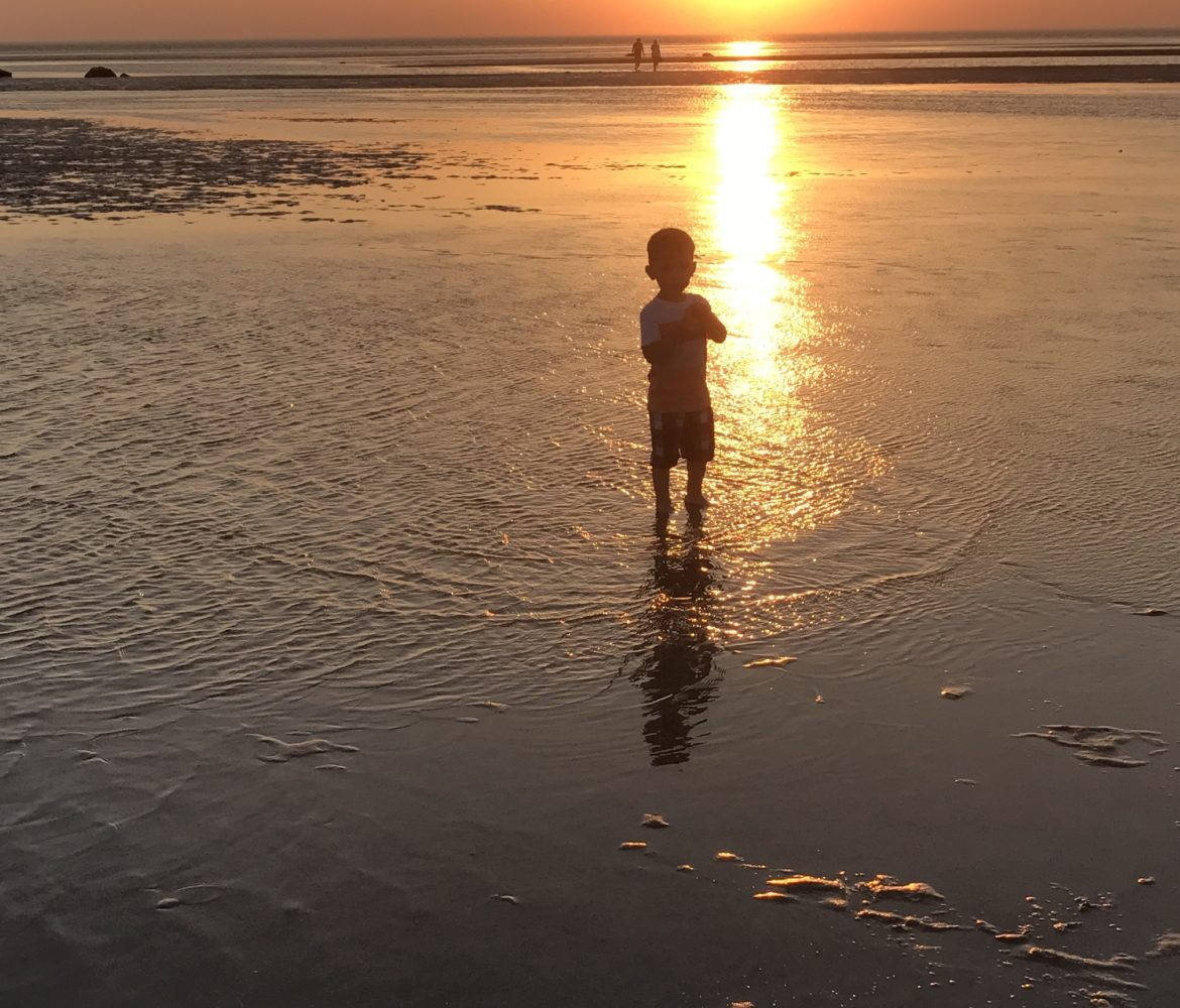 Small boy in shallow water on flats at sunset